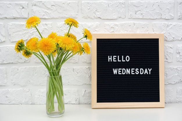 Hello wednesday words on black letter board and bouquet of yellow dandelions flowers