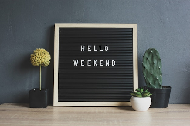 Hello weekend quote on blackboard with cactus, succulent and decorative plant on wooden table