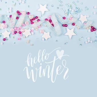 Hello winter с милым украшением: кружевной лентой, звездами, пайетками и розовыми жемчужными бусинами на синем фоне. плоская планировка, вид сверху.