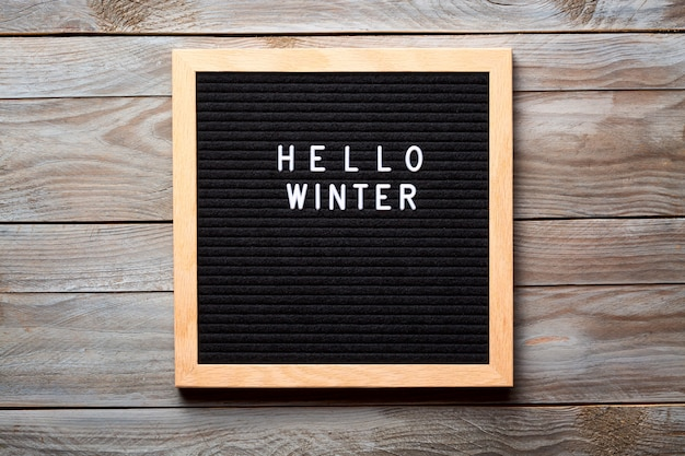 Hello winter words on a letter board on wooden background