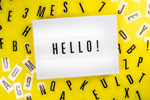 Hello word on lightbox on scattered alphabet letters background