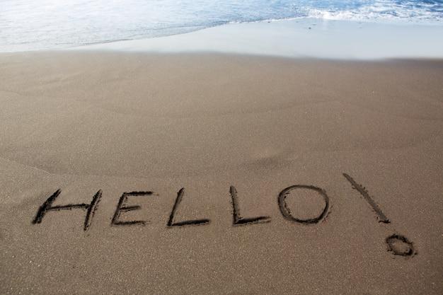 Коричневый песчаный пляж с письменным словом hello