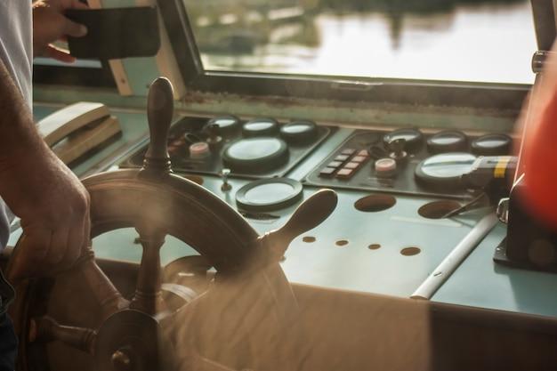 Штурвал корабля на переднем плане, пока командир ведет корабль на переправе по реке.
