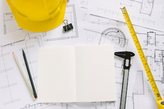 Helmet and drafting supplies on blueprints
