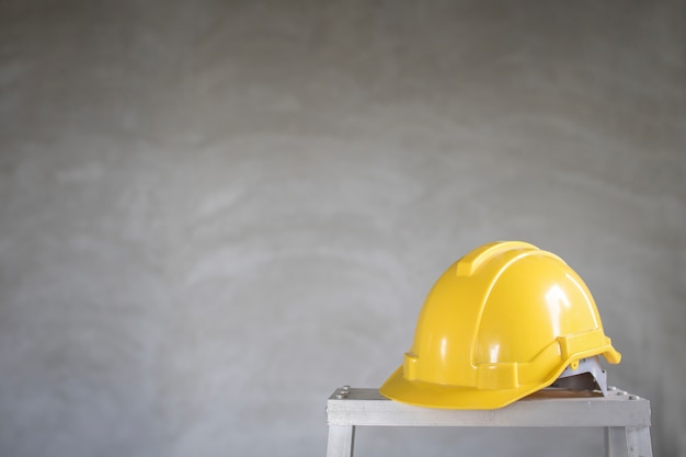 Helmet construction on stair with cement wall background, copy space.