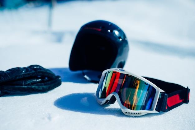 雪のクローズアップのヘルメット、メガネ、手袋、誰も。冬の極端なスポーツコンセプト。マウンテンスキー用具