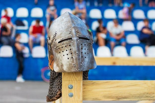 観客と表彰台の背景に中世の騎士のヘルメット_