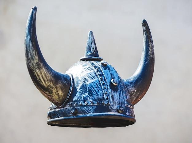 灰色の背景に中世の戦士のヘルメット、角のある騎士のヘルメット