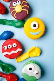 Heloweenデザート:テーブルの上のアイシングとキャンディーの目のクローズアップとビスケットマカロンで作られた面白いモンスター。