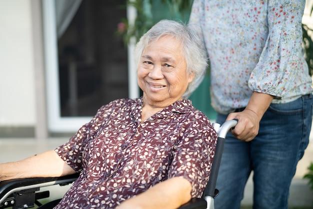 自宅で車椅子に座っているアジアのシニアまたは高齢の老婦人女性患者、健康的な強力な医療コンセプトを支援し、ケアします。