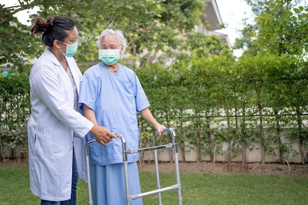 アジアの高齢者または高齢者の老婦人女性が健康で歩行器を使用するのを助け、ケアする