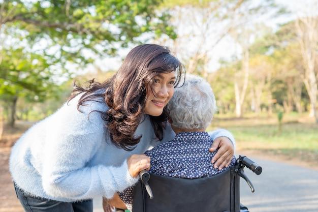公園でアジアの年配の女性患者を助け、ケアします。
