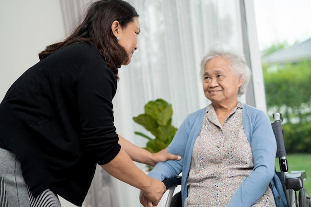 病院で車椅子に座っているアジアの年配の女性患者のヘルプとケア