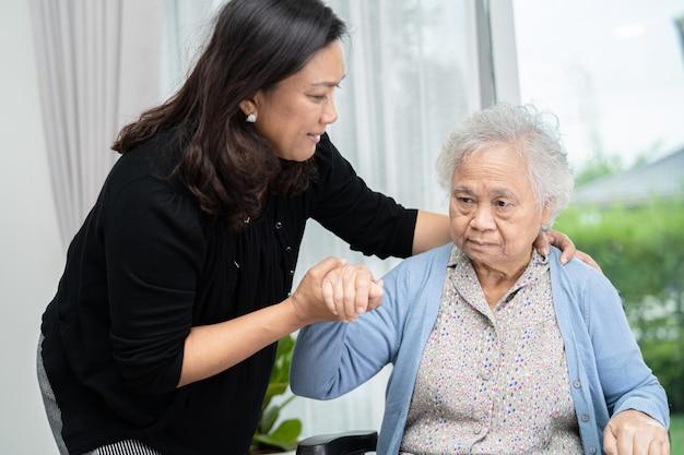病院で車椅子に座っているアジアの年配の女性患者を助け、世話をする