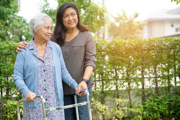 アジアの年配の女性が公園で歩行器を使用するのを手伝ってください。