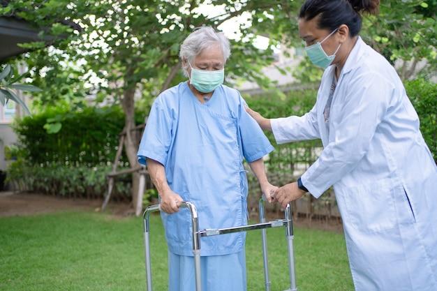 公園を歩いている間、アジアの年配の女性が歩行器を使用するのを手伝ってケアする