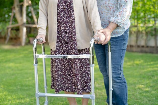 도움과 보살핌 아시아 노인 여성은 공원에서 걷는 동안 강한 건강을 가진 워커를 사용합니다