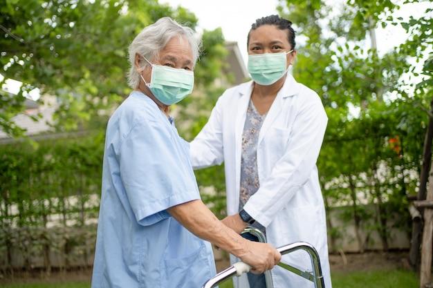 公園を歩いている間、アジアの年配の女性が強い健康で歩行器を使用するのを手伝ってケアする