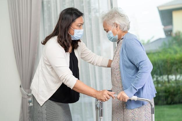 アジアの年配の女性が病院を歩いている間、健康の強い歩行器を使用するのを手伝ってケアする