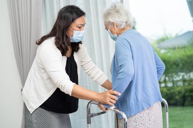アジアの年配の女性が歩きながら健康の強い歩行器を使用するのを手伝ってケアする