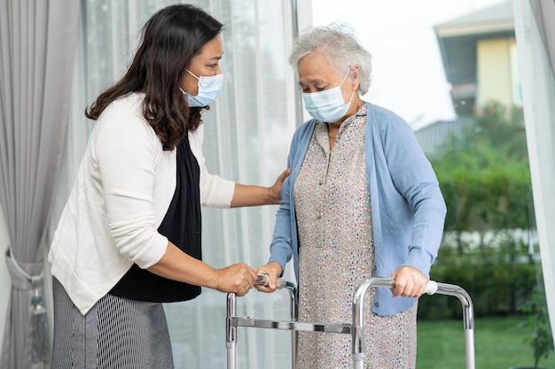 アジアの年配の女性が健康で歩行器を使用するのを手伝ってケアする