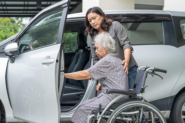 アジアのシニアまたは高齢の老婦人女性患者が彼女の車に乗る準備をするのを手伝ってサポートしてください。