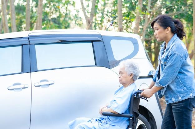Помогите и поддержите азиатского старшего пациента женщины сидя на кресло-коляске подготовьте получить к ее автомобилю.