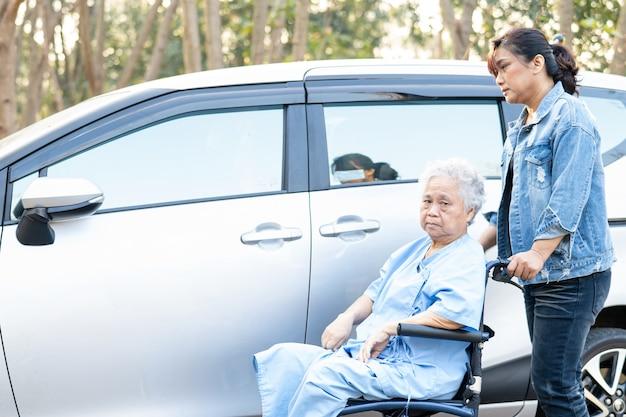車椅子に座っているアジアの年配の女性患者が彼女の車に乗る準備をするのを手伝ってサポートする