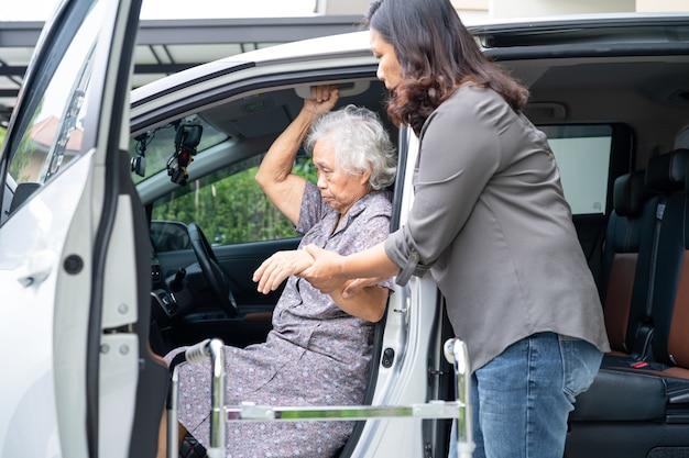歩行器でアジアの年配の女性患者の歩行を支援し、彼女の車に乗る準備をします