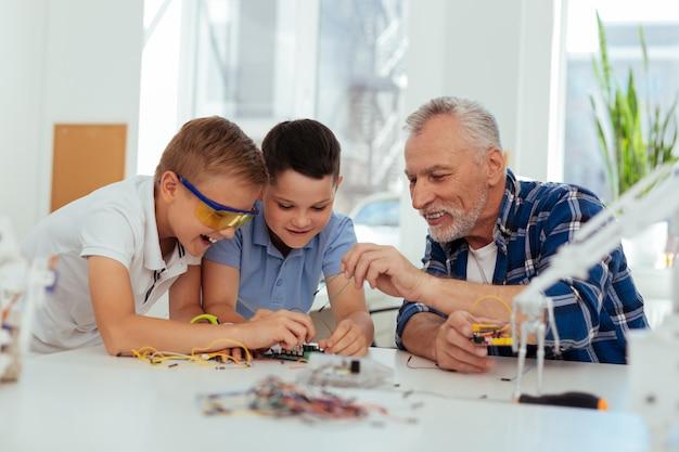 Помощь и поддержка. позитивный радостный учитель сидит вместе со своими учениками, помогая им построить робота