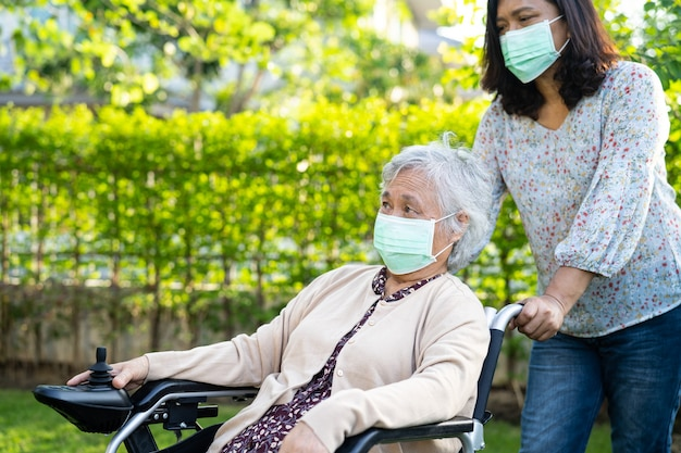Help asian senior or elderly old lady woman on electric wheelchair and wearing a face mask for protect safety infection covid-19 coronavirus in park.