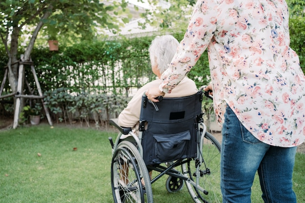 Help asian senior or elderly old lady woman on electric wheelchair and wearing a face mask for protect safety infection covid 19 coronavirus in park