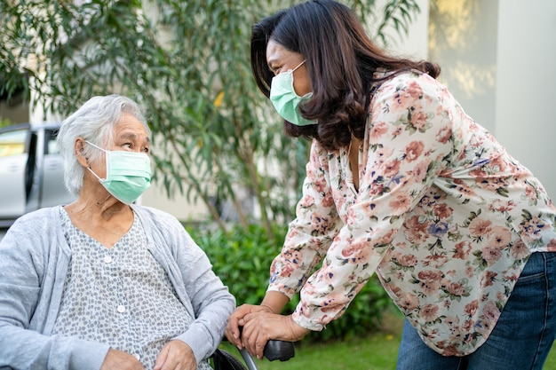 Help asian senior or elderly old lady woman on wheelchair and wearing a face mask for protect safety infection covid-19 coronavirus in park.