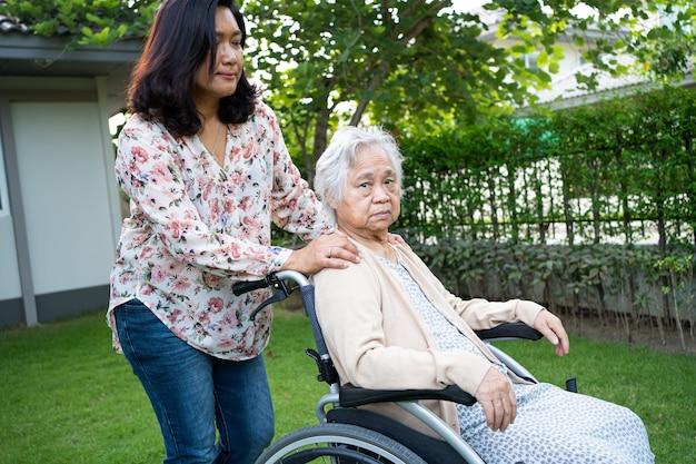 電動車椅子に乗ってフェイスマスクを着用し、安全感染を防ぐためにアジアの高齢者または高齢者の老婦人を助ける公園内のcovid19コロナウイルス