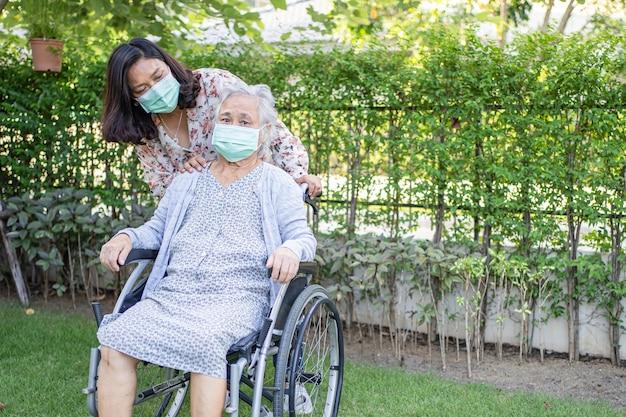 車椅子で、公園でコロナウイルスを保護するためのフェイスマスクを身に着けているアジアの年配の女性を助けます