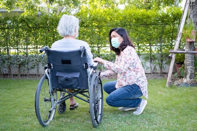 コロナウイルスを保護するために車椅子でフェイスマスクを着用しているアジアの年配の女性を助けます