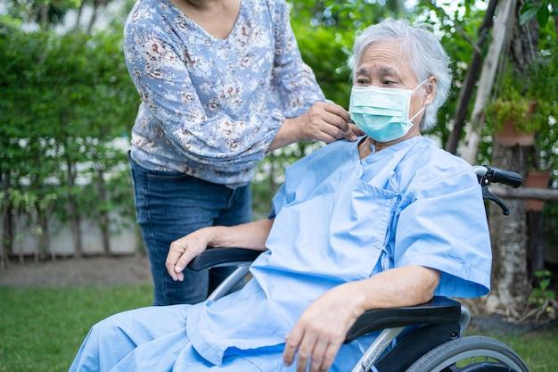 Covid19コロナウイルスを保護するために車椅子でフェイスマスクを着用しているアジアの年配の女性を助けます