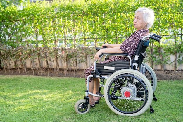 公園で電動車椅子でアジアの年配の女性患者を助ける