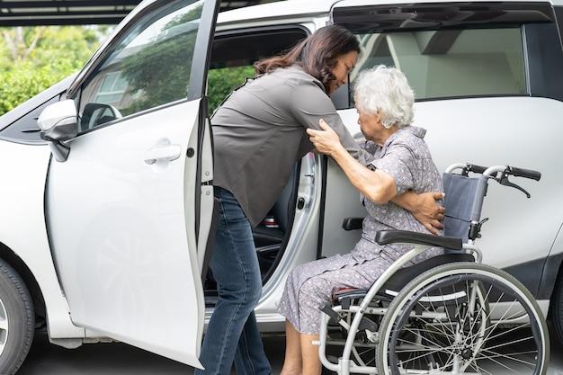 車椅子に座っているアジアの年配の女性患者が彼女の車に着く準備をするのを手伝ってください