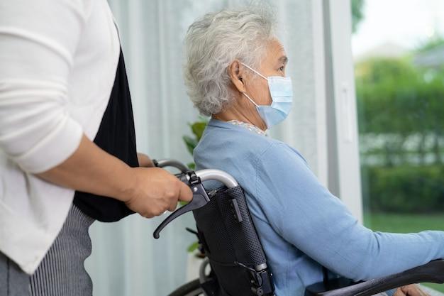 コロナウイルスを保護するために車椅子に座ってフェイスマスクを着用しているアジアの年配の女性を助けます