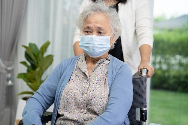 コロナウイルスを保護するために車椅子に座ってマスクを着用しているアジアの年配の女性を助けます