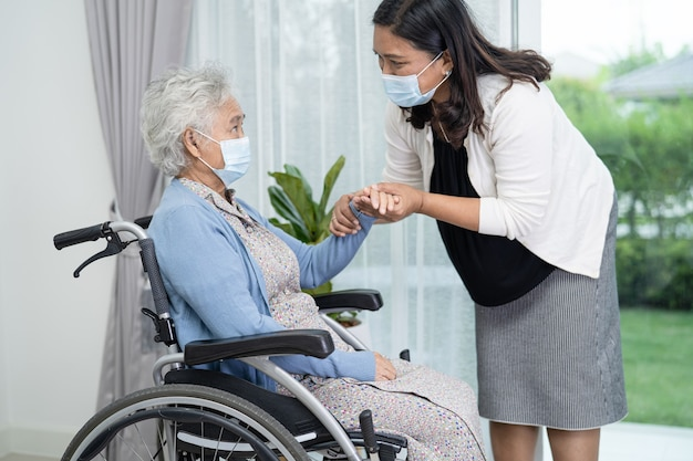 Help asian senior woman sitting on wheelchair and wearing mask for protect infection coronavirus