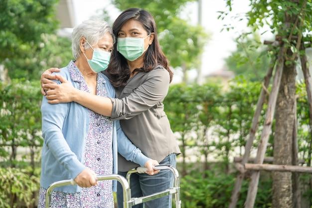 アジアの年配の女性がコロナウイルスを保護するために歩行器とマスクを着用して歩くのを手伝ってください