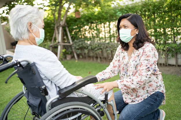 Help asian senior woman on wheelchair and wearing a mask for protect covid19 coronavirus in park