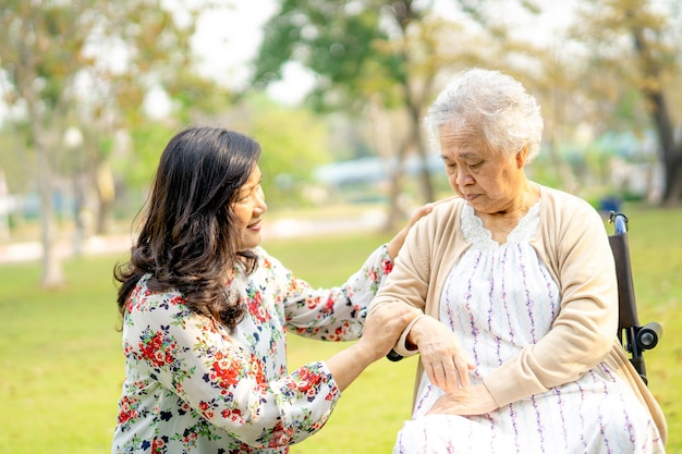 Help and care asian senior woman patient in park.