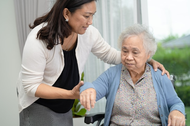 Help and care asian senior woman patient sitting on wheelchair at hospital ward
