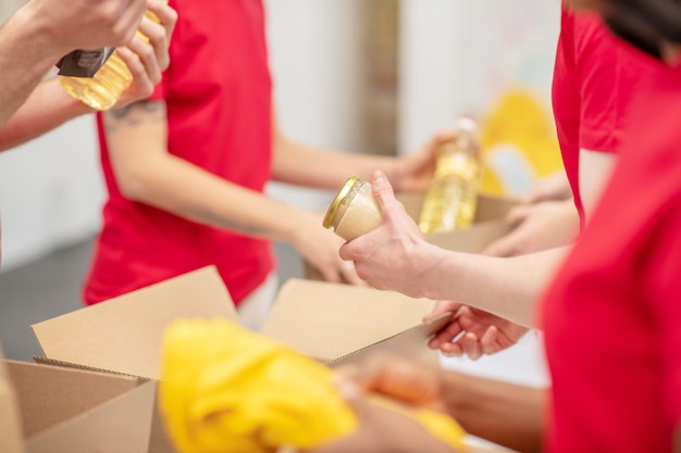 Помощь, благотворительность. руки молодых людей в одинаковых красных футболках упаковывают еду и одежду в картонные коробки в благотворительной организации