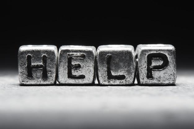 Концепция помощи. надпись на металлических кубах 3d, изолированные на черном фоне, стиль гранж