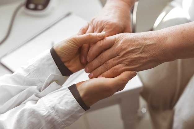 Помощь пожилым людям. руки пожилой женщины. врач поддерживает пациента.