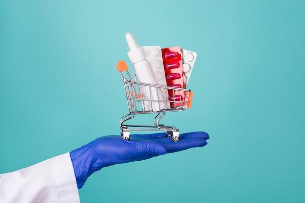 患者の概念を支援します。ティールターコイズの背景に分離された薬のブリスターと小さなカートを保持しているゴムラテックス手袋で手にドキュメントのクローズアップトリミング写真